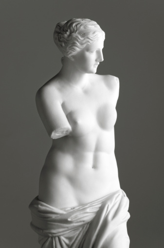 Vintage copy statue of Venus (Aphrodite) de Milo, a famous Greek sculpture dating back to about 100 BC, discovered in 1820 on the Aegean island of Milos. The original statue is in the Louvre museum in Paris. Vintage-styled fine art image on a grey background with added light grain.