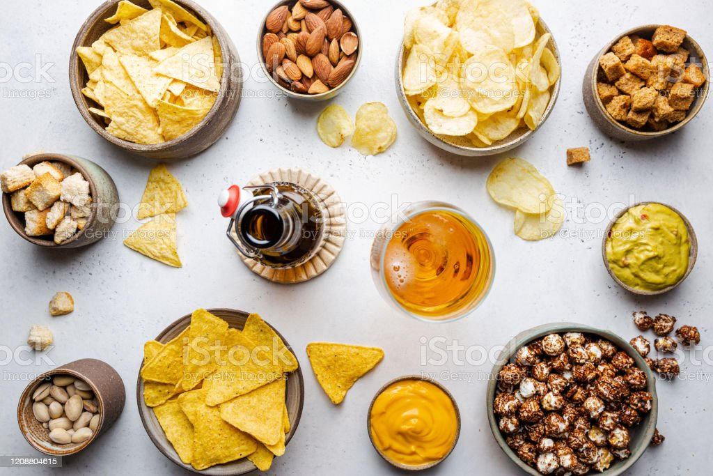 Veraity bowls of beer snacks Veraity bowls of beer snacks and sauces on stone table. Nuts, chips, nachos, crackers. Top view with copyspace Alcohol - Drink Stock Photo