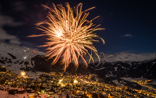 Fireworks above the mountains on New years eve in the Swiss alps Ski resort of Verbier, famous for its party lifestyle.