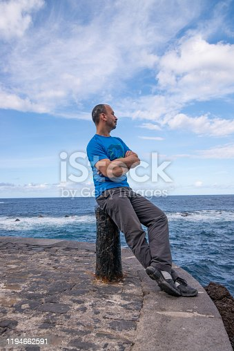 Verical Portrait of Adult Man Looking At View Sitting on Post at Old Port with Arms Crossed Garachico, Tenerife, Canary Islands, Spain - stock photo