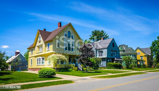 A row of well maintained, colorful,  19th century Queen Anne Victorian  style homes along a quiet street   in a northern Vermont small town.
