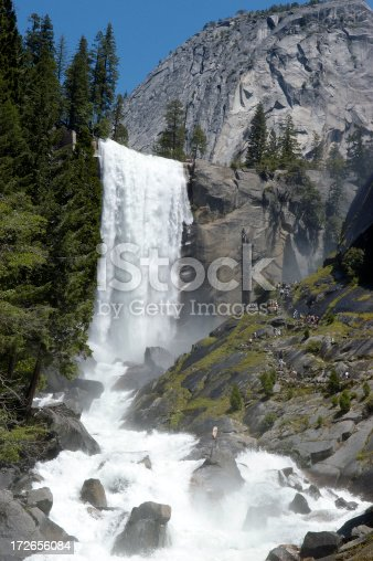 Vernal falls view showing the trail on the mountain side leading to the top of the waterfall.  If you look closely you can see many people walking the misty trail to the top.  Seeing the people allows the viewer to understand the sheer size of the area in the photo.