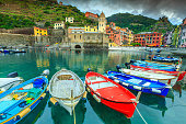 Stunning cloudy evening, famous Vernazza touristic place with fantastic harbor and colorful wooden fishing boats, Cinque Terre, Liguria, Italy, Europe
