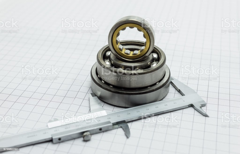 Vernier caliper lying on drafting paper with bearing. stock photo