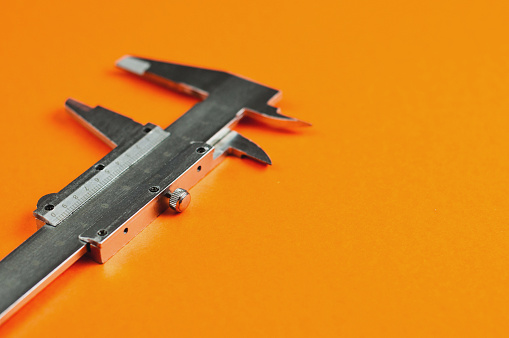 istock Vernier caliper of gray color on orange table with copy space for your text 1046891476