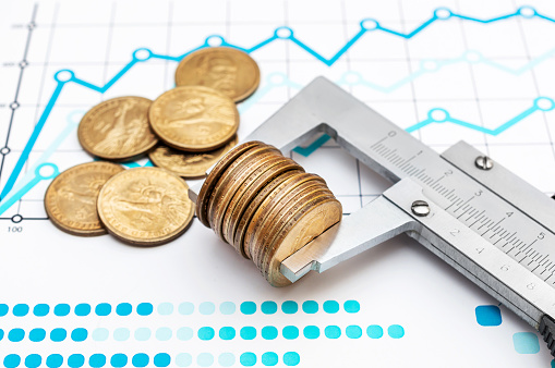 istock Vernier caliper with coins on business chart and graph. Business and financial concept. 1176973748
