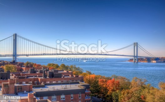 HDR - High Dynamic Range Image (photorealistic) of the bridge and lush foliage, lit by autumn morning sun. The Verrazano-Narrows Bridge connects boroughs of Brooklyn and Staten Island in New York City. The bridge was built in 1964 and is the largest suspension bridge in the USA. The bridge took over the title of the longest suspension bridge in the world (previously held by the Golden Gate Bridge) from 1964 until 1981, when it was eclipsed by the Humber Bridge in England.