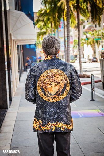 Rodeo Drive, Beverly Hills, CA - Aug 2, 2017. Elegant man wearing Versace silk shirt with logo of Medusa walks on Rodeo Drive