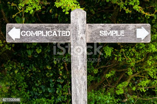 Wooden signpost with two opposite arrows over green leaves background. SIMPLE versus COMPLICATED directional signs, Choice concept image