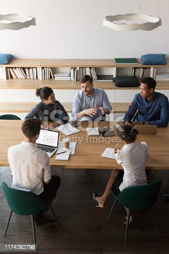 istock Vertical above view diverse business people negotiating in boardroom 1174262798