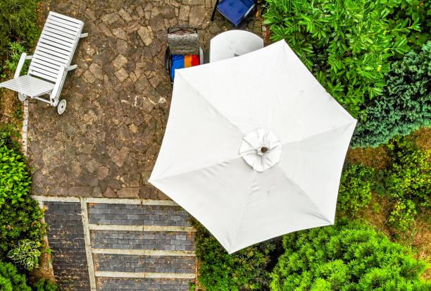 vertikale luftaufnahme des hellen sonnenschirm auf der terrasse, aus der nähe aufgenommen mit der drohne. - sonnenschirm terrasse stock-fotos und bilder