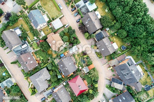 1095367134 istock photo Vertical aerial view of a suburban settlement in Germany with detached houses, close neighbourhood and gardens in front of the houses. 993441560