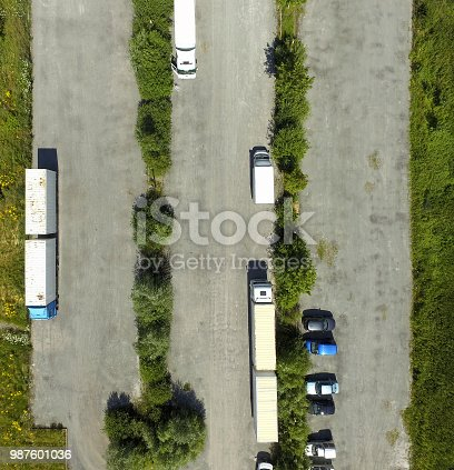 1095367134 istock photo Vertical aerial view of an almost empty asphalted grey parking lot with two trucks and cars 987601036