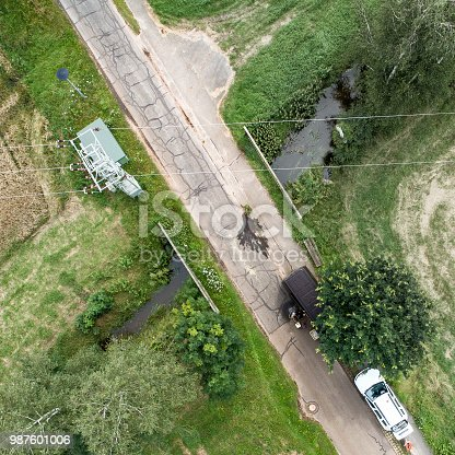1095367134 istock photo Vertical aerial view of the crossing of a stream under a narrow street with a power cable above it 987601006