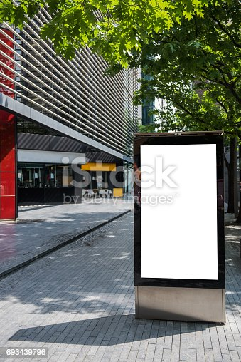 istock Vertical billboard with advertising space and copy space on white display screen photographed outdoors 693439796