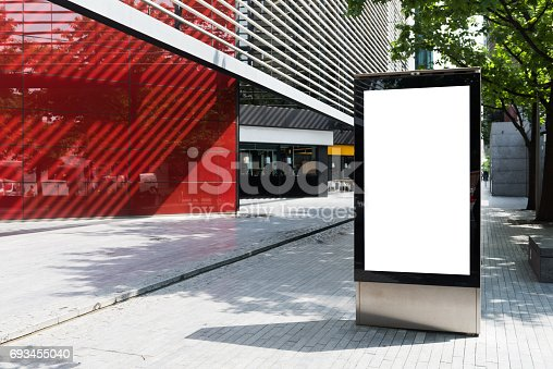 693455040 istock photo Vertical billboard with advertising space and copy space on white display screen photographed outdoors 693455040