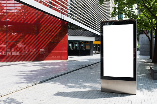 istock Vertical billboard with advertising space and copy space on white display screen photographed outdoors 693455040