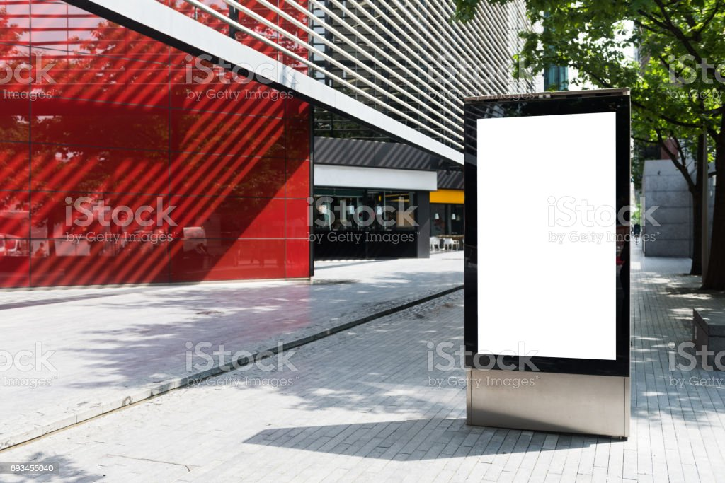 Vertical billboard with advertising space and copy space on white display screen photographed outdoors stock photo