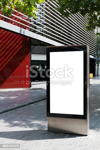 istock Vertical billboard with advertising space and copy space on white display screen photographed outdoors 693455076