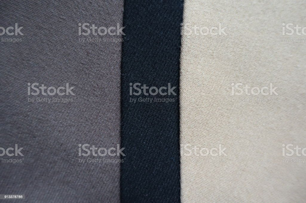Vertical black ribbon sewn between grey and beige fabric stock photo