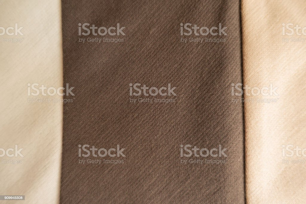 Vertical brown stripe sewn to beige fabric stock photo