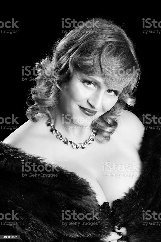 Vertical B&W of smiling blond in fur. royalty-free stock photo