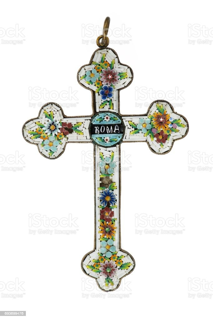 Vertical closeup of an old cross with a handmade floral ornament made of beads and gems stock photo