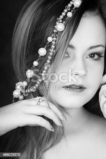 Vertical B&W closeup studio shot on dark gray background of young woman, 18 years old, with subtle natural makeup. Looking at camera with hands close to face, wearing pearl ring with pearl and sparkly necklace in hair.