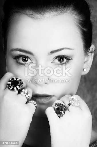 Vertical B&W closeup studio shot on gray of young woman, 18 years old, with soft subtle natural makeup and several sparkly rings, hands up touching face. Big eyes with gentle, serious expression.