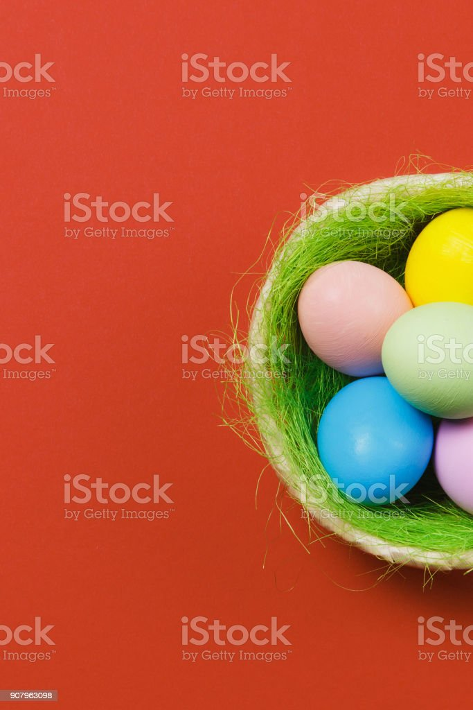 Vertical colorful pastel monophonic painted Easter eggs in basket with green grass isolated on red background. Happy Easter concept. Copy space for advertisement. With place for text. Top view on eggs stock photo