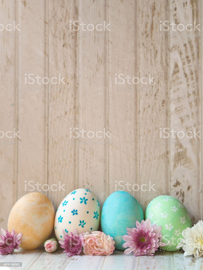 Vertical copy space and background of hand painting Easter eggs with white, yellow, blue and green color egg shells and pink and white color Spring flowers on vintage white wooden table background stock photo