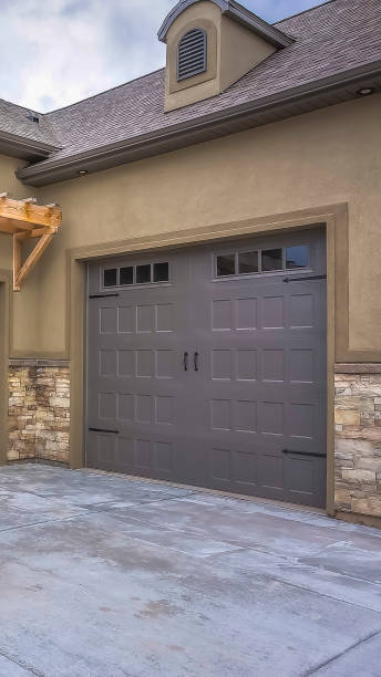 Vertical Exterior of a home with view of gray double garage doors and stone wall stock photo