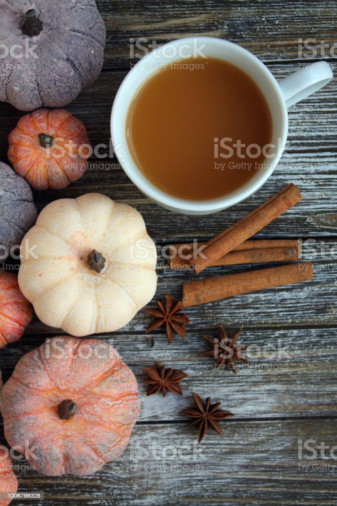 white mug of coffee top view. With aged pumpkins and cinnamon sticks...