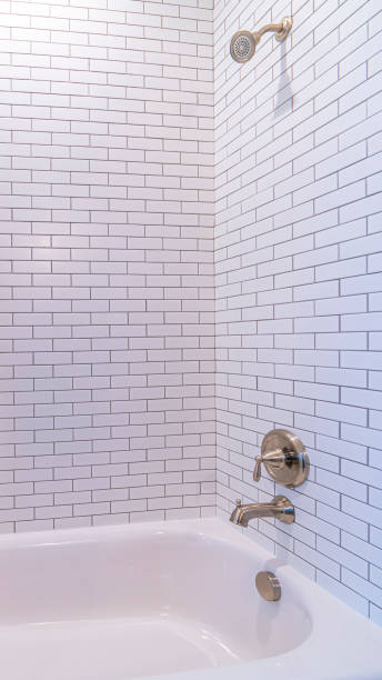 Vertical frame Clean white tiled shower combination tub bright interior stock photo