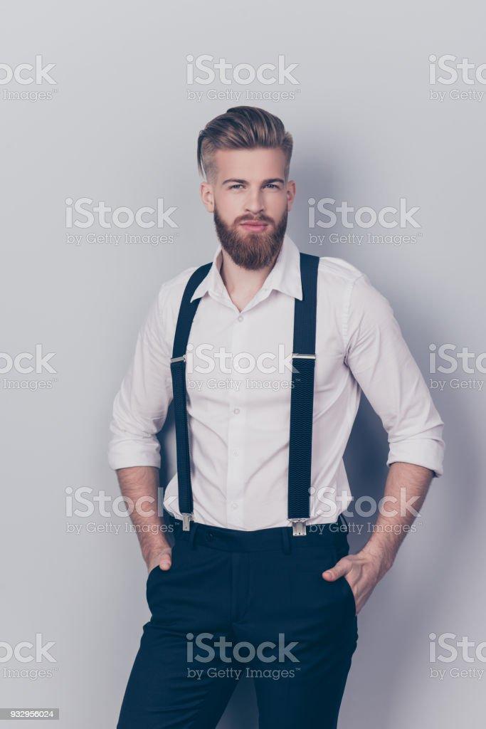 Avant vertical Découvre le portrait de chic chic chic confiant ciblée concentré superbe riche riche macho avec des cheveux blonds, garder les mains au look sexy poches isolée sur fond gris - Photo