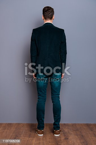 Vertical full length body size rear back behind view portrait of his he trendy fashionable guy wearing velveteen blazer dark jeans near over gray violet purple pastel background wall.