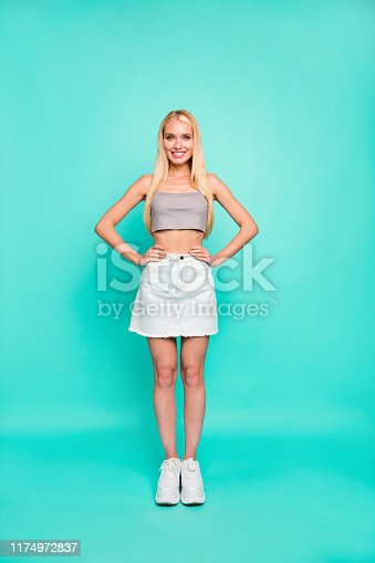 Vertical full length body size view of nice attractive lovely gorgeous, content cheerful sportive straight-haired girl posing streetstyle isolated on bright vivid shine green blue turquoise background