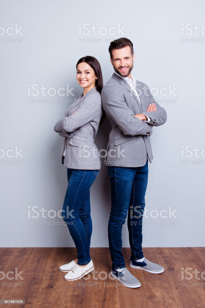 Vertical full-length photo of two businesspeople standing with crossed hands against gray background stock photo