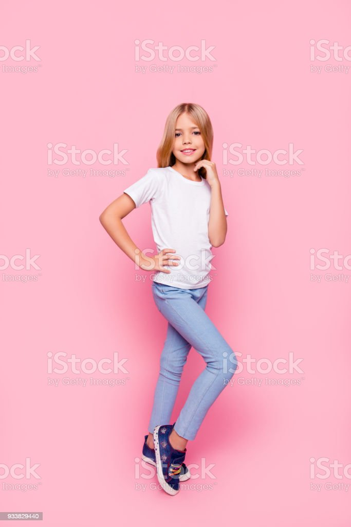 Vertical full-length portrait of cute sweet lovely adorable beautiful with beaming toothy smile charming pre teen girl holding hands near chin on waist standing isolated bright vivid pink background stock photo