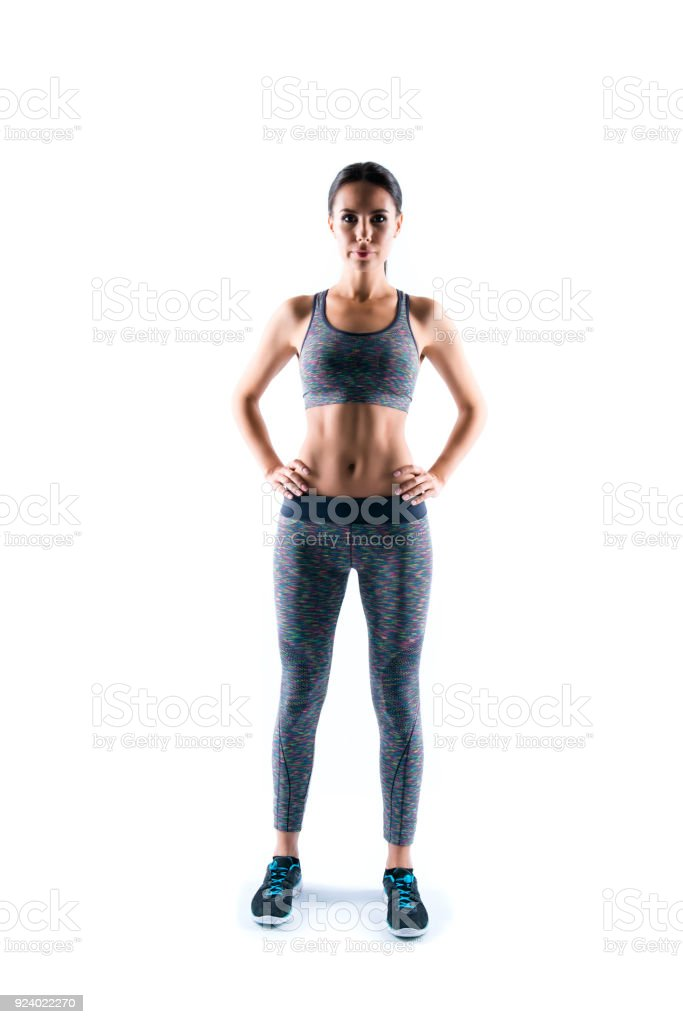Vertical full-size full-lenght portrait of confident concentrated serious beautiful sporty woman's figure wearing top and stretching pants for doing exercises, isolated on white background stock photo