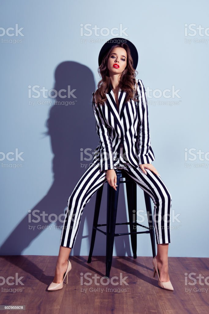 Vertical full-size full-length front view portrait of attractive charming well-dressed flirty coquettish lovely gorgeous emancipated dreamy lady posing on chair isolated on gray background stock photo
