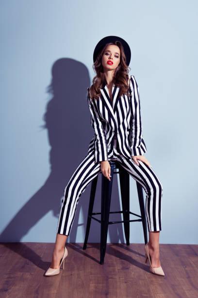 vertikale full-size-full-length vorderansicht porträt attraktive charmante wohlgekleidete flirty kokett schöne wunderschöne emanzipierte verträumte dame posiert auf stuhl auf grauem hintergrund isoliert - bein make up stock-fotos und bilder