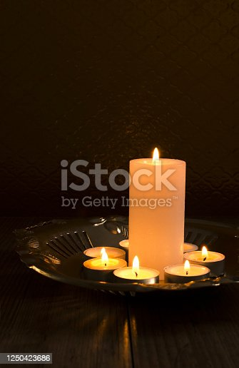 Warm and calm atmosphere.Candles on the golden tray against glass background.Empty space