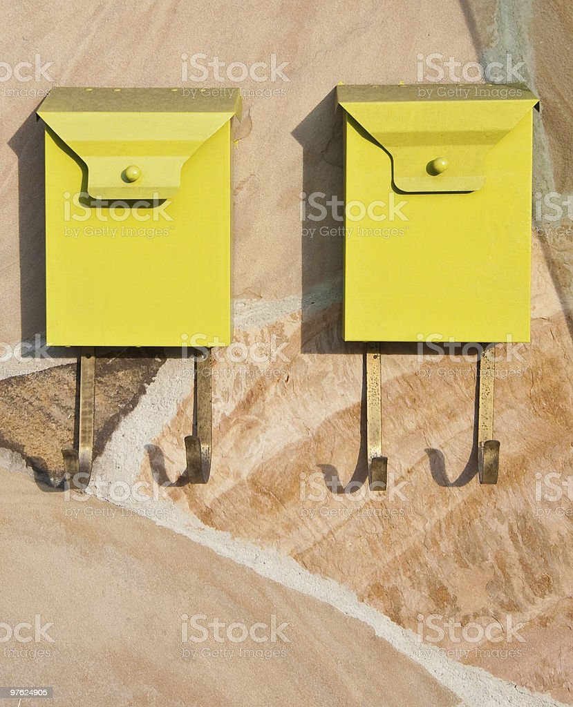 Vertical Image of Two Metal Yellow Mailboxes on Flagstone Wall royalty-free stock photo