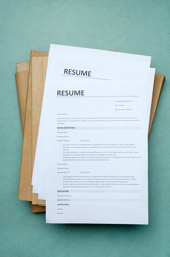 Vertical image.Top view of stack of resume forms and folders on the office blue desk