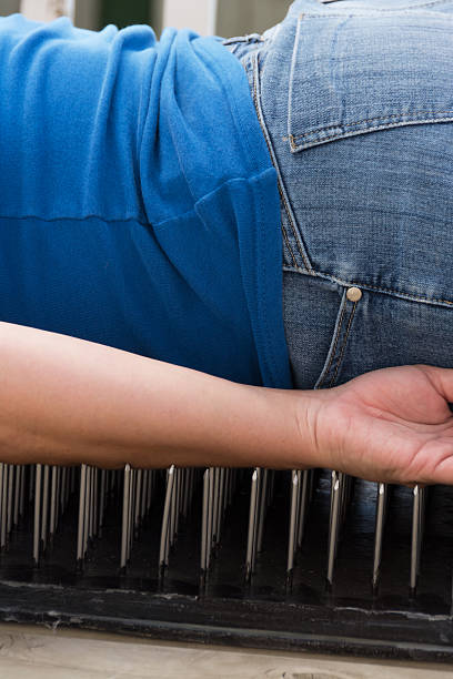 Vertical midsection, woman laying on bed of nails stock photo