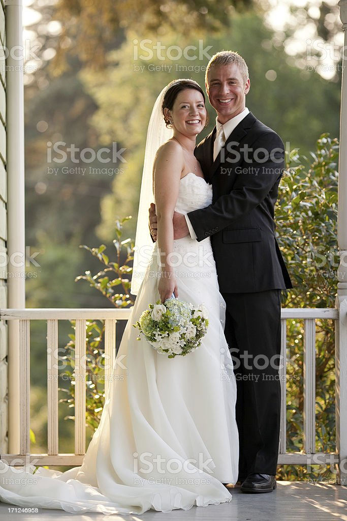 Vertical Newlyweds Posing Together On Country House Porch Wooded Background stock photo