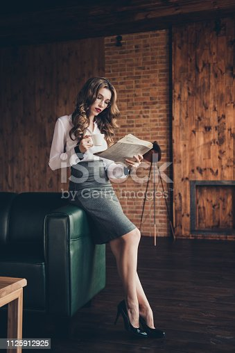 Vertical of nice attractive lovely slim elegant graceful classy charming dreamy wavy-haired lady agent broker daily paperwork routine at workplace station loft interior