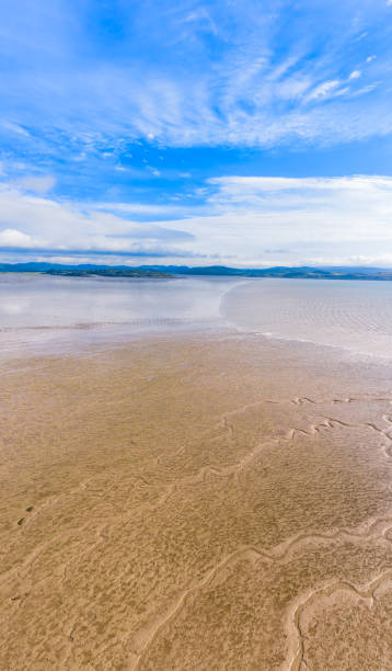 Vertical panoramic view of sand as the tide comes in on a bright sunny morning in south west Scotland The view on a bright sunny summer day across Auchencairn Bay. The location is in Dumfries and Galloway south west Scotland. Beyond the bay is the Solway Firth, a stretch of water between the north west coast of England and the south west coast of Scotland. The image was created by merging three images captured by a drone. johnfscott stock pictures, royalty-free photos & images