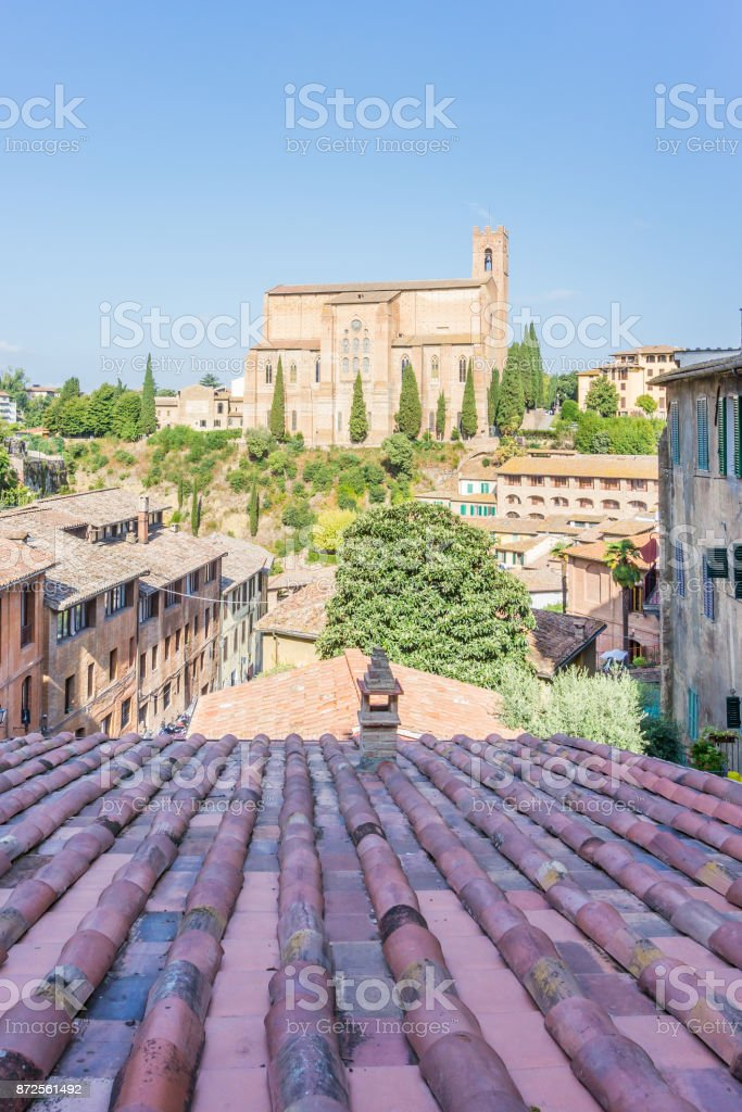 Vertical photo of ancient church which is on the hill with few cypress trees. The old houses and buildings are on both sides of picture. View is over old red roof. Church is in Siena in Italy. stock photo